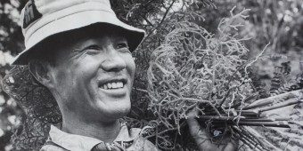 Old photo of asian man working on hawaiian trail
